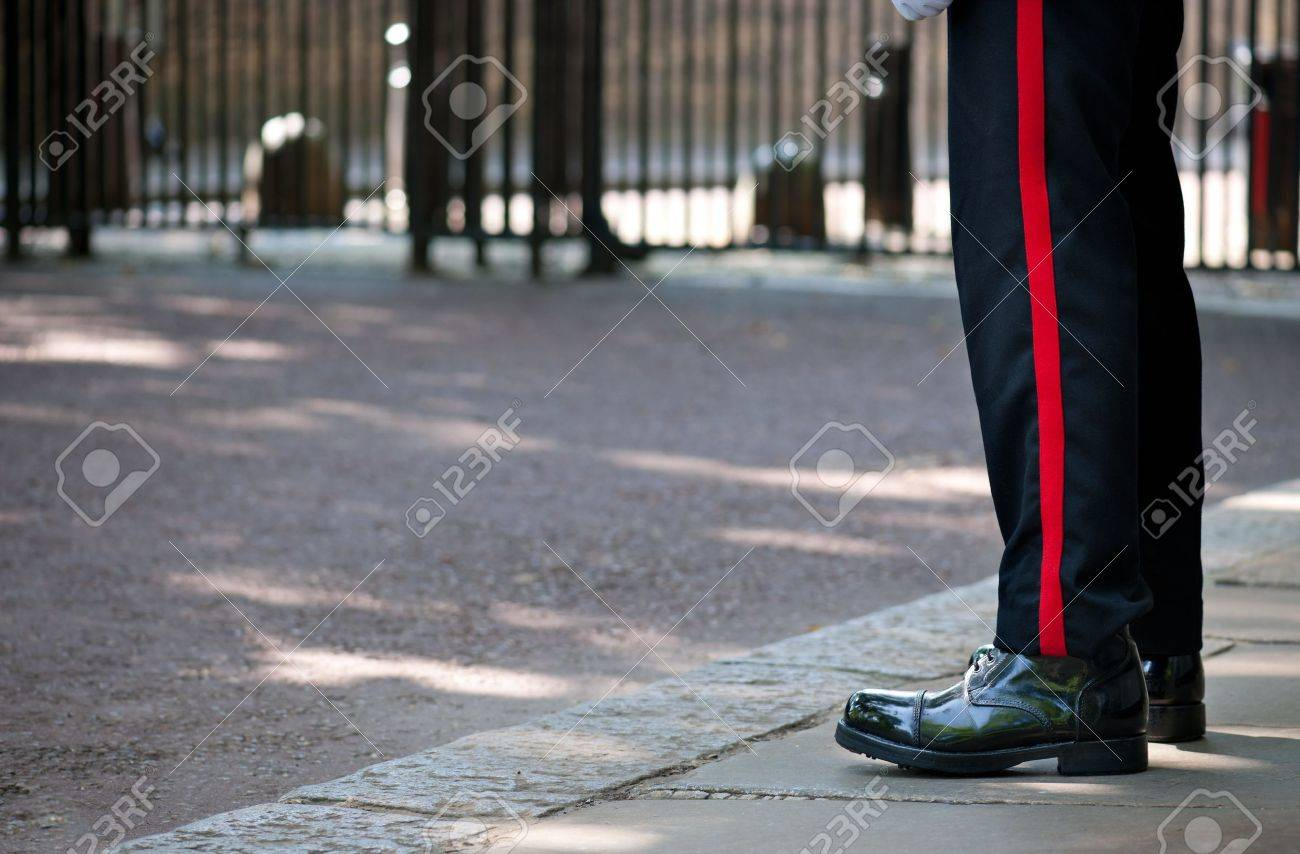 Shiny red boots soldier of the british royal guard watching an entry of buckingham