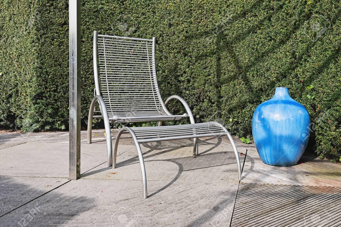 banque dimages chaise de jardin moderne avec repose pieds et vase dcoratif bleu avec une haie de conifres en arrire plan