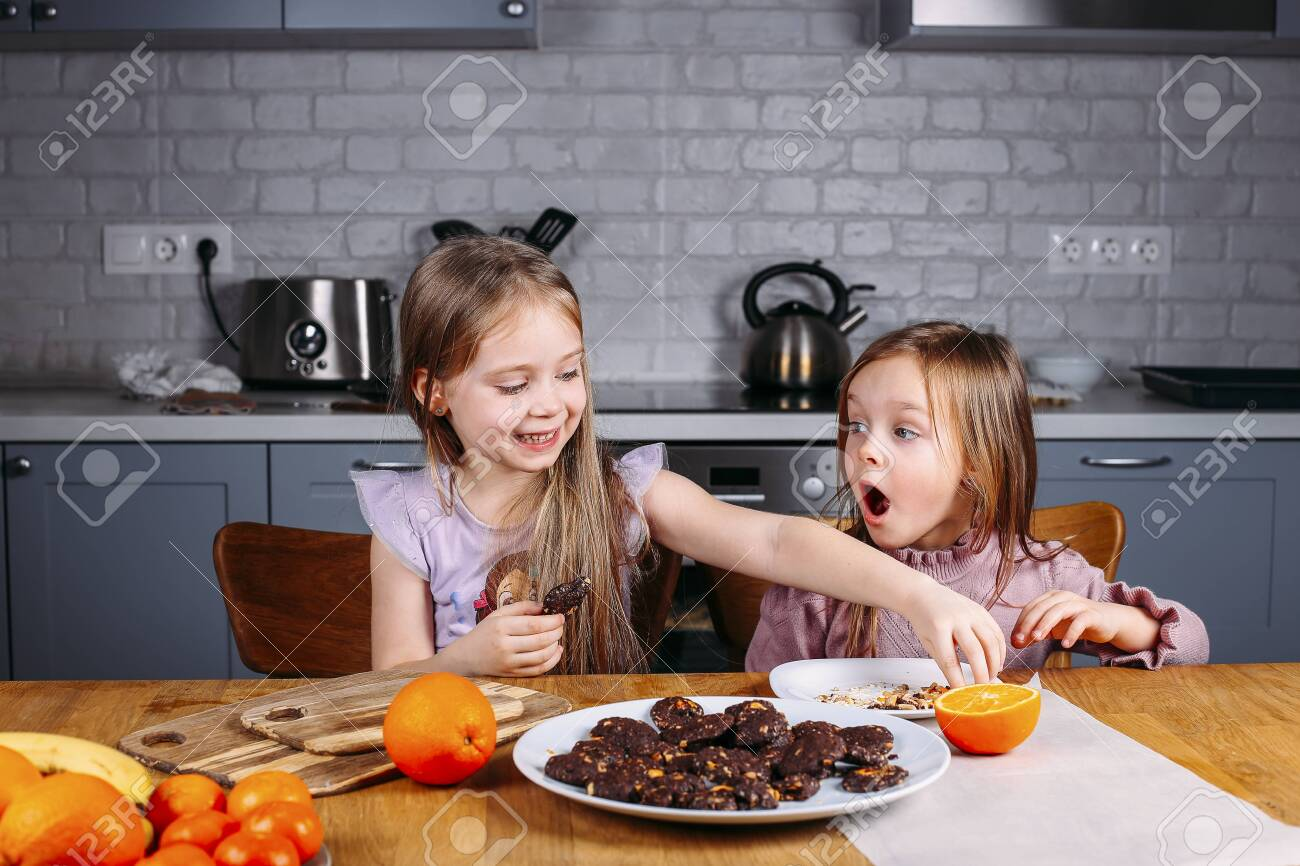 Young small girls eating biscuits at home. Playing and feeding themselfs - 143215654