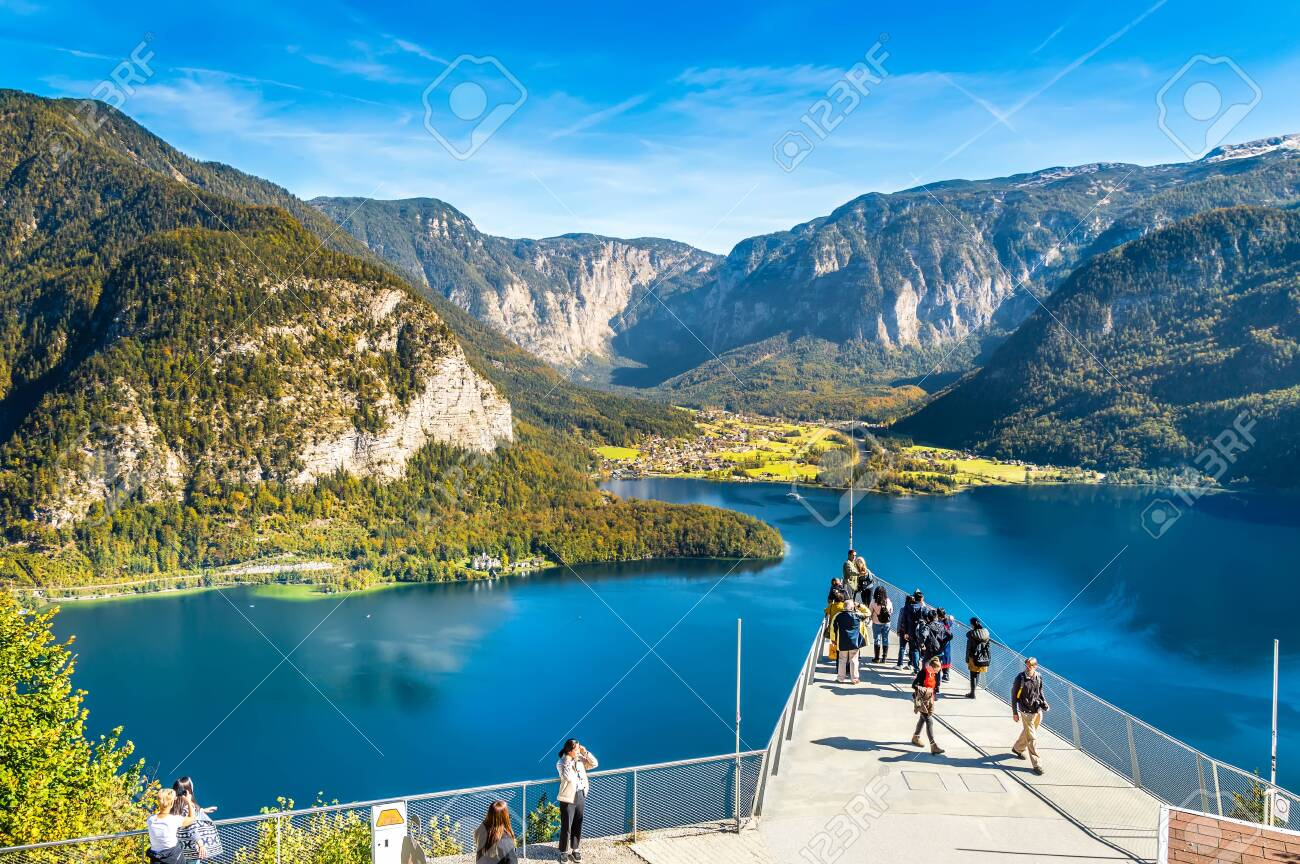 Hallstatt, Austria - OCT 2018: Tourists take photos and enjoy the view of the mountains and lake Hallstatter See from the World Heritage View Point. Popular tourist destination in Austrian Alps. - 133913400