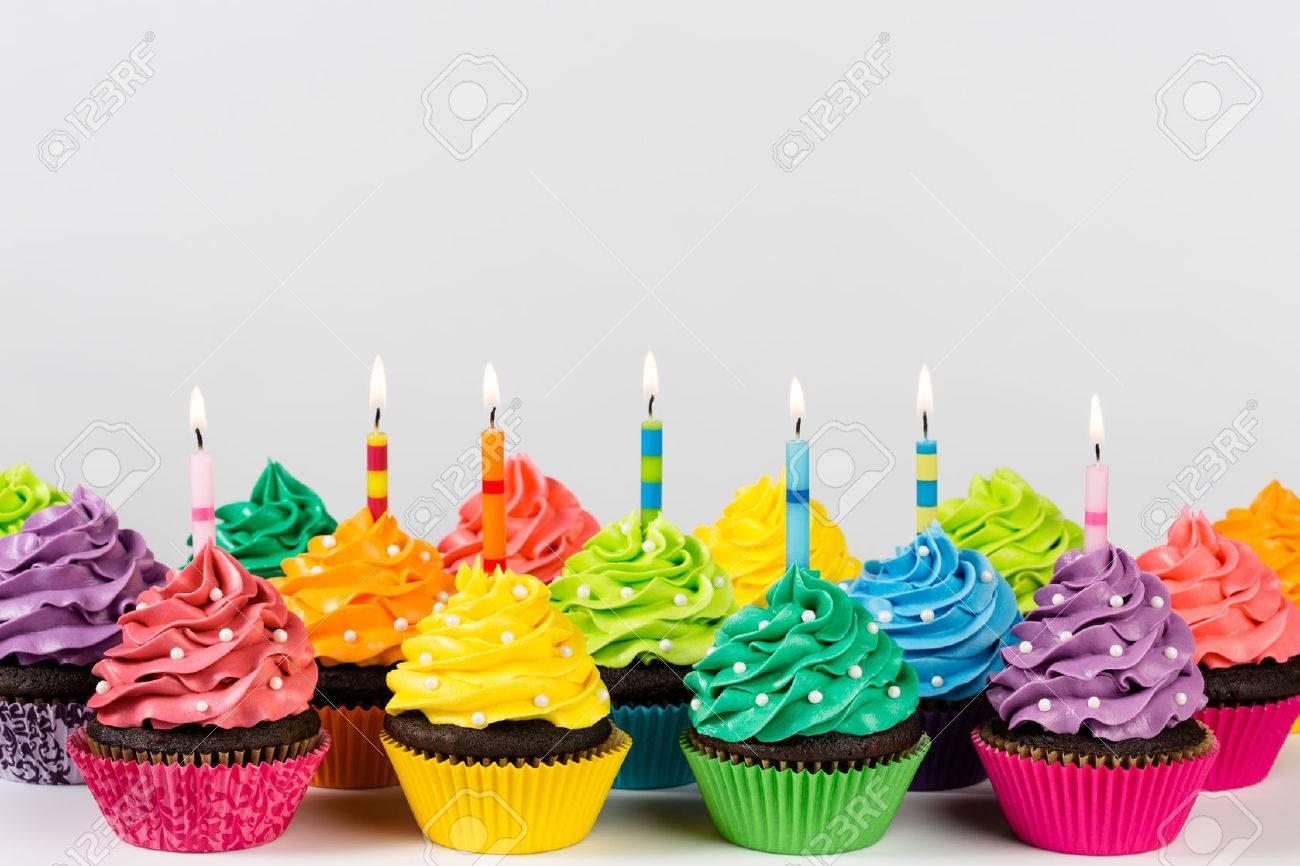 Filas De Cup Cakes Decorados Con Coloridas Velas De Cumpleaños Y Rocía