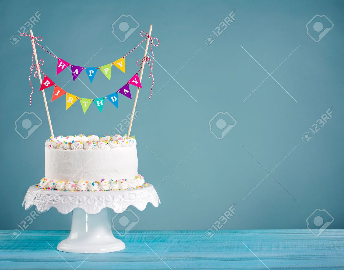 White Buttercream Birthday Cake With Colorful Bunting And Sprinkles