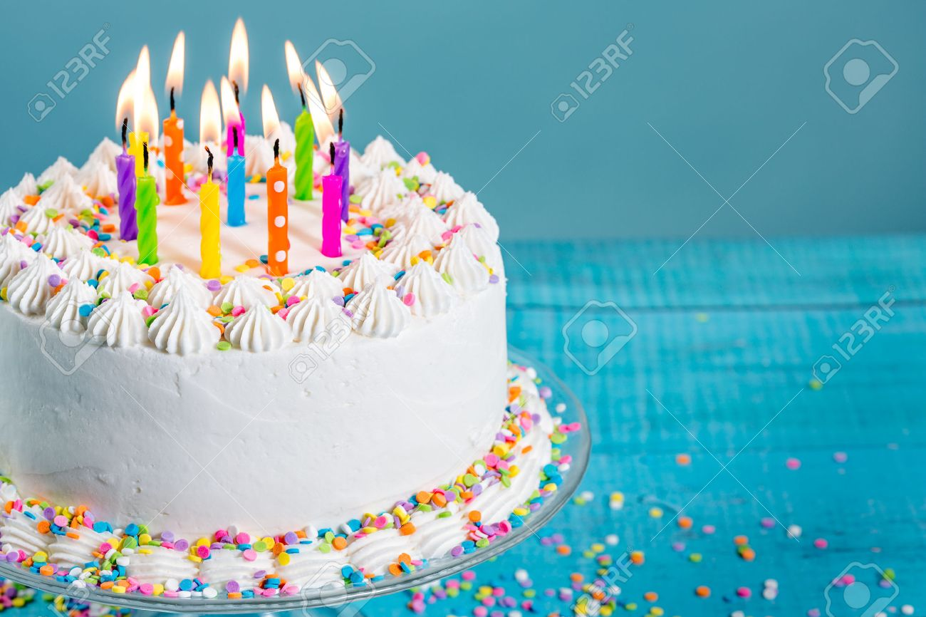 White Buttercream icing birthday cake with with colorful sprinkles and Candles over blue background - 52937248
