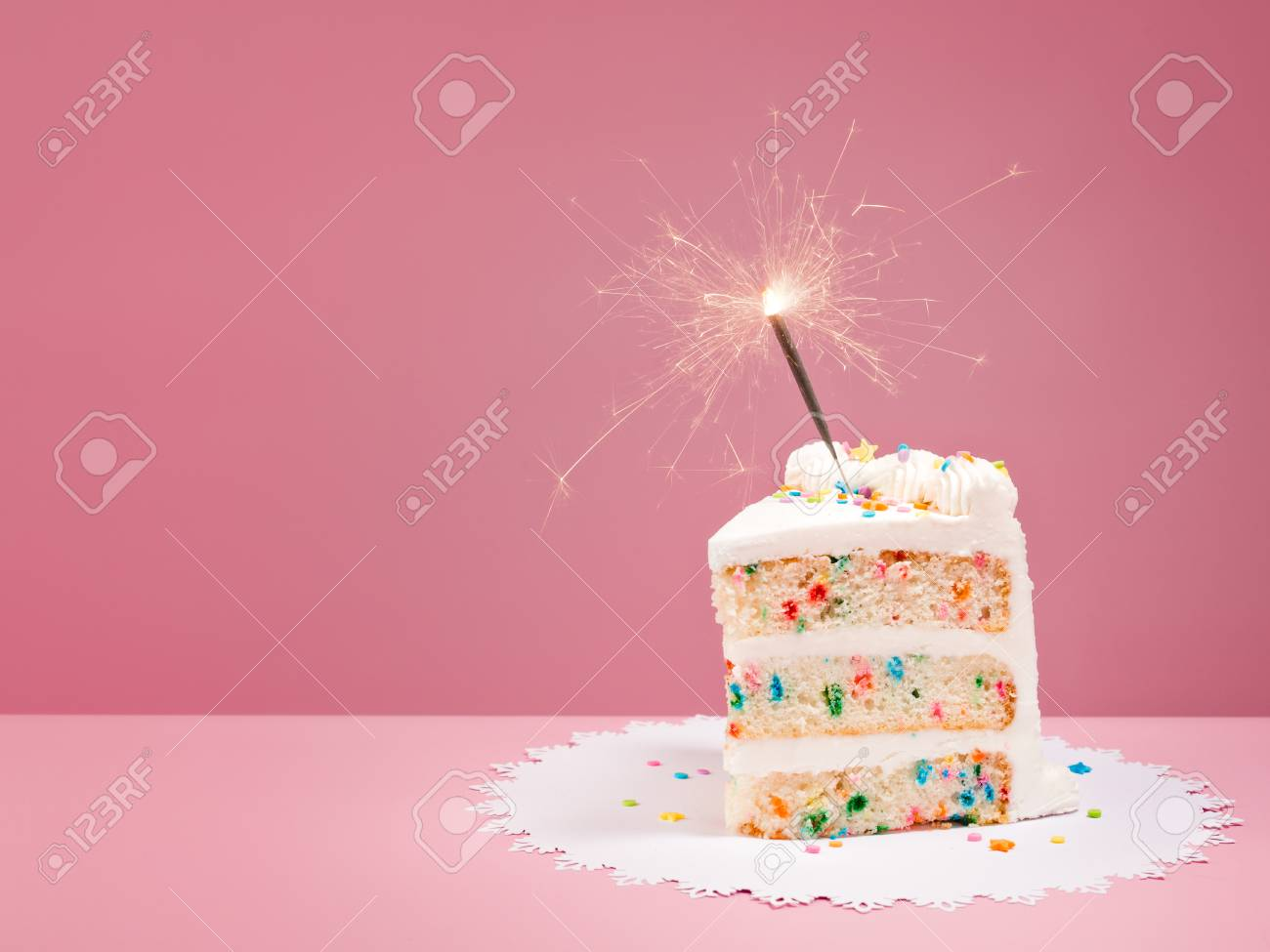 Slice Of Colorful Birthday Confetti Cake With A Lit Sparkler Over Pink Background Stock