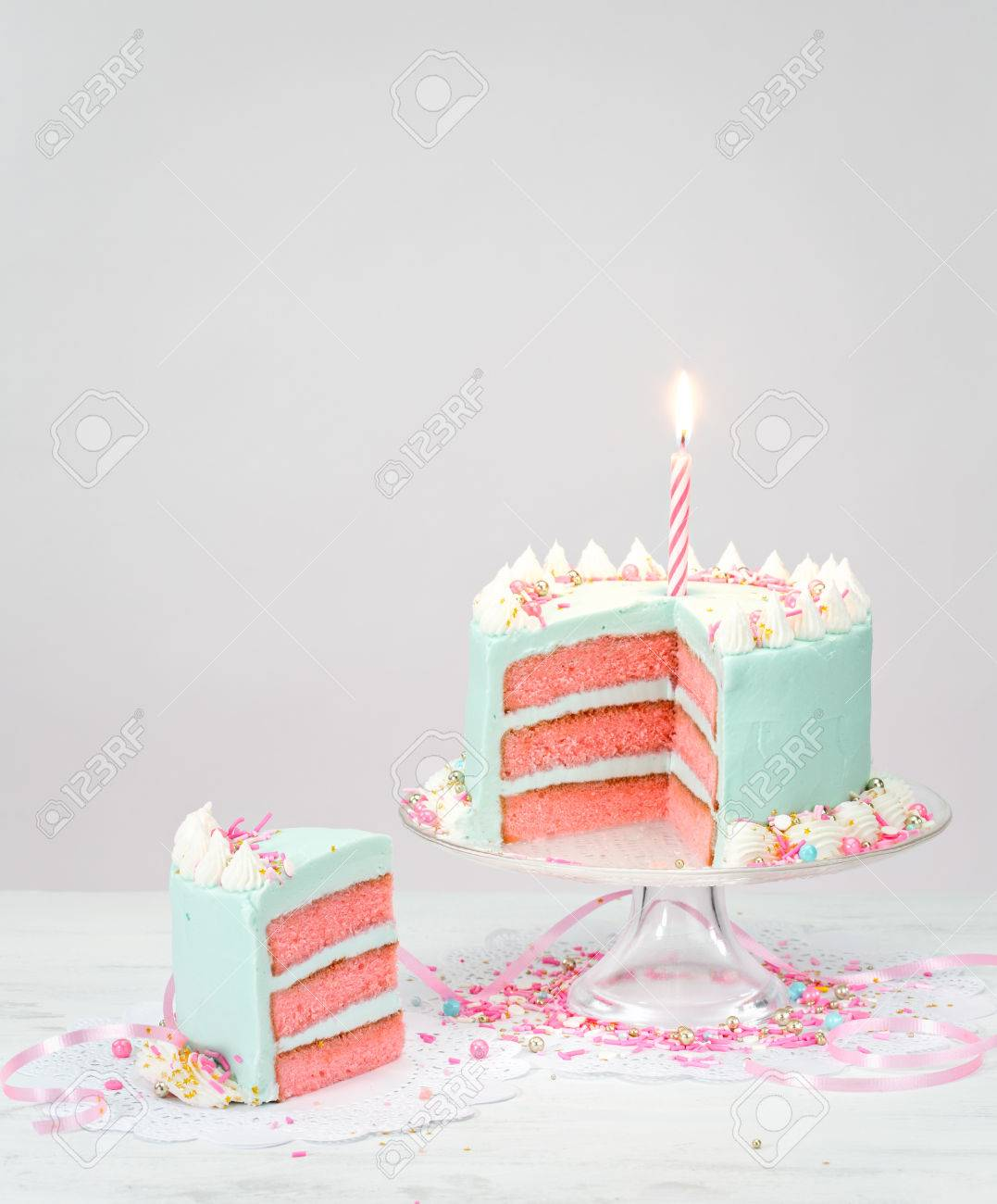 Pastel Blue Birthday Cake Over White Background With Pink Layers And Sprinkles Stock Photo