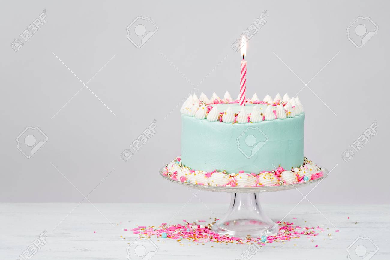 Pastel Blue Birthday Cake Over White Background With Pink Sprinkles Stock Photo
