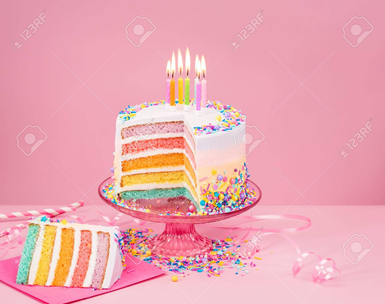 Colorful Rainbow Birthday Cake And With Candles Over A Pink Background Stock Photo