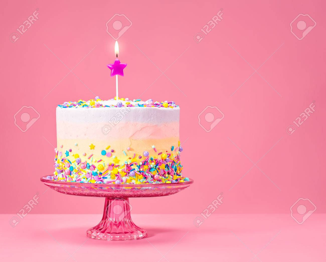 Colorful Birthday Cake With Sprinkles Over A Pink Background Stock Photo