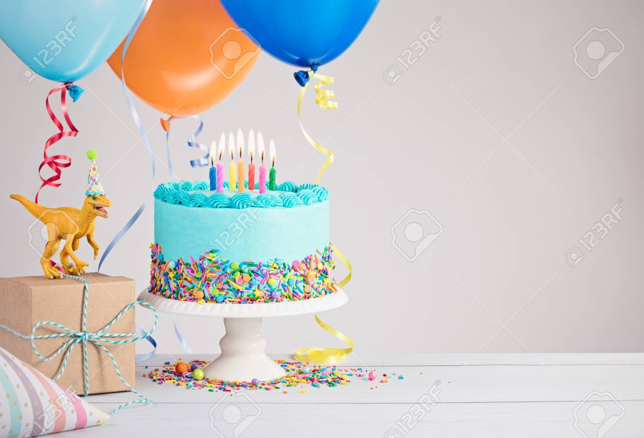 Childs birthday party scene with blue cake, gift box, toy dinosaur, hats and colorful balloons over light grey. - 78949765