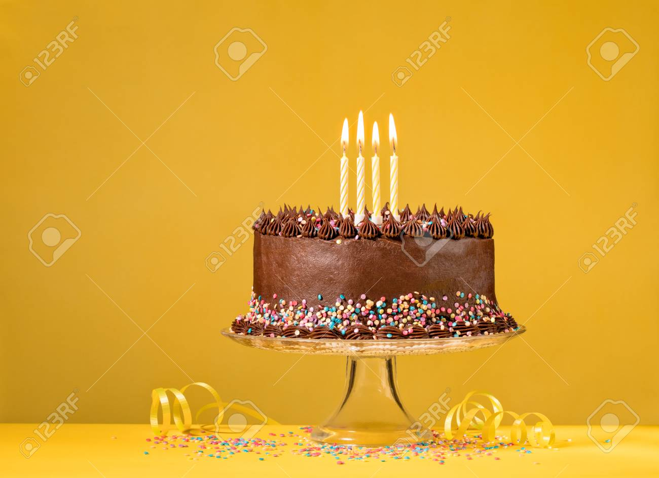 Chocolate Birthday Cake With Colorful Sprinkles And Candles Over Yellow Background Stock Photo
