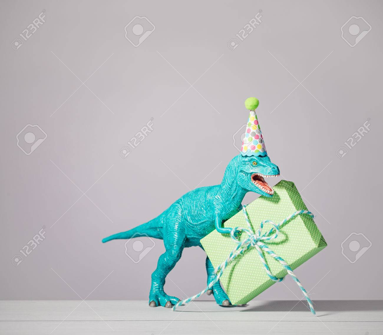 T Rex Dinosaur Toy With Birthday Hat Holding Gift On A Light Stock