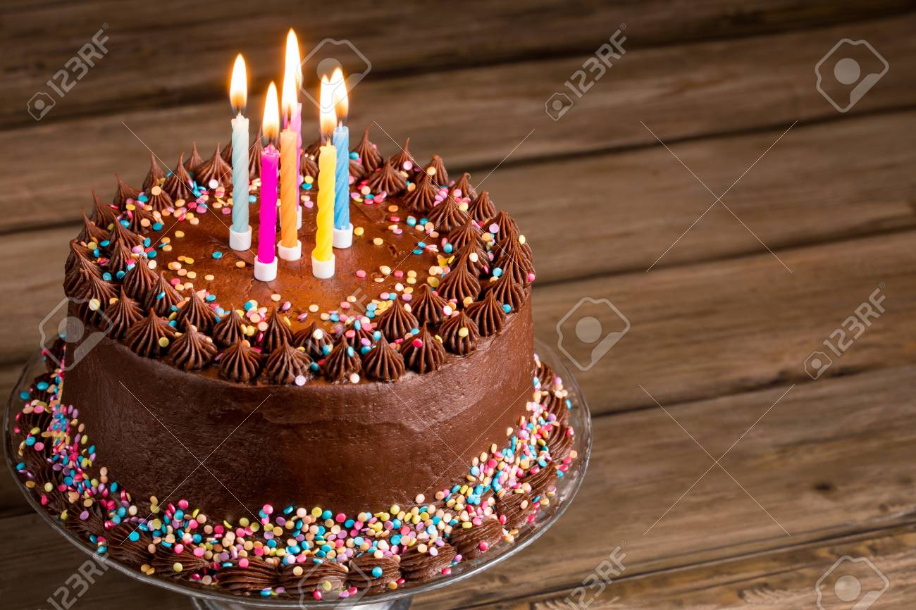 Chocolate Birthday Cake With Colorful Sprinkles And Candles Over