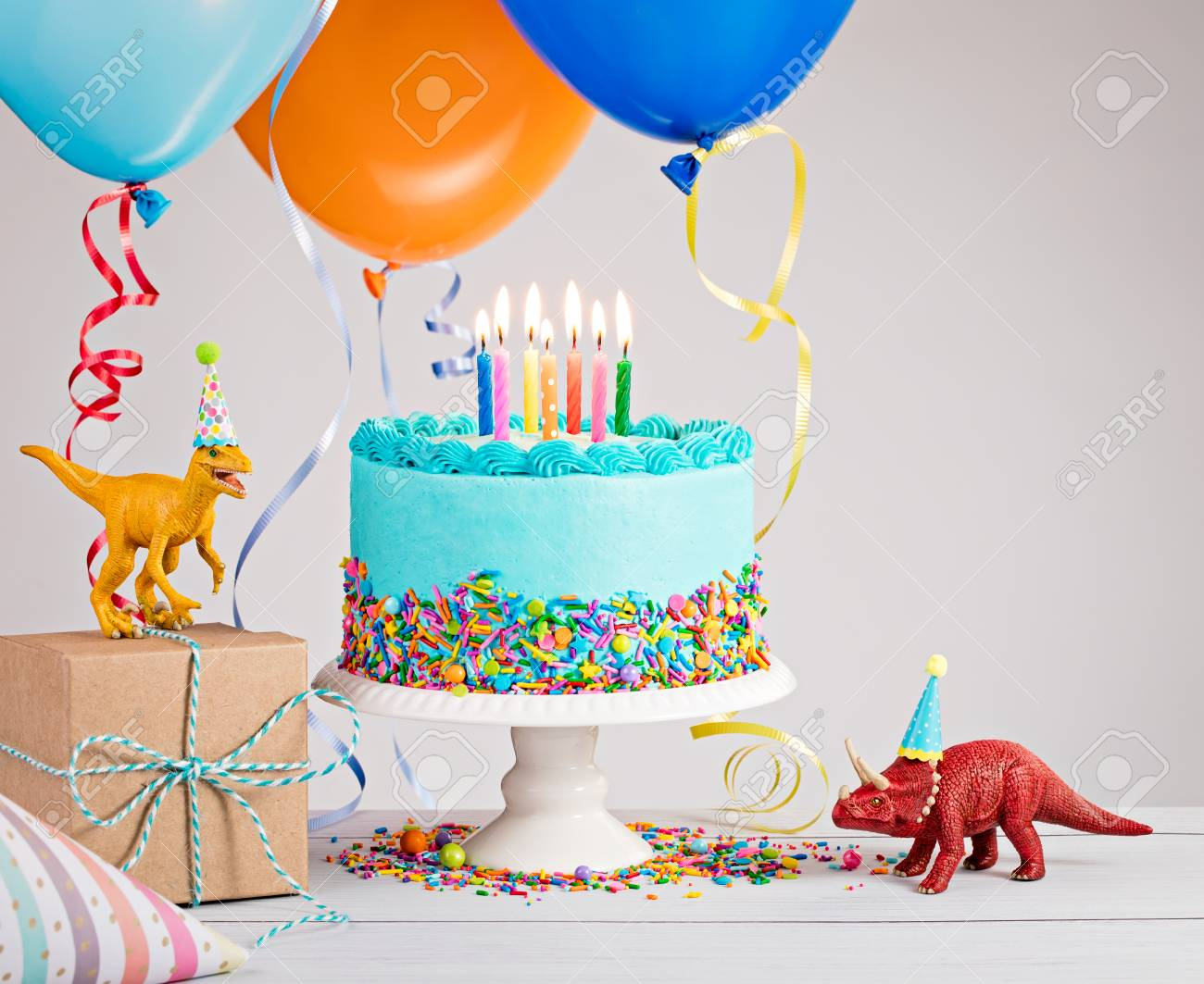 Childs Birthday Party Scene With Blue Cake Gift Box Toy Dinosaurs