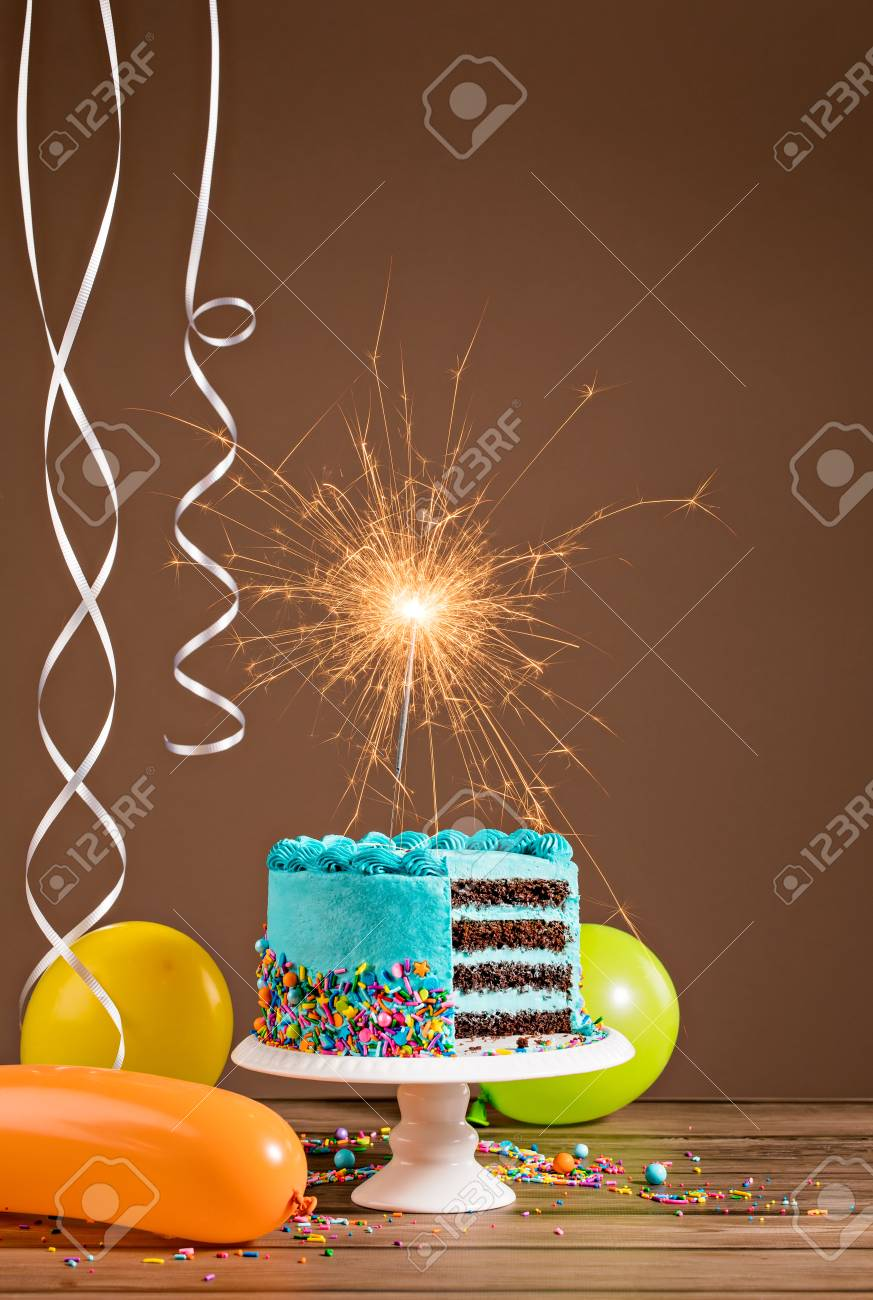 Blue Birthday Cake With Sparkler And Colorful Balloons Stock Photo