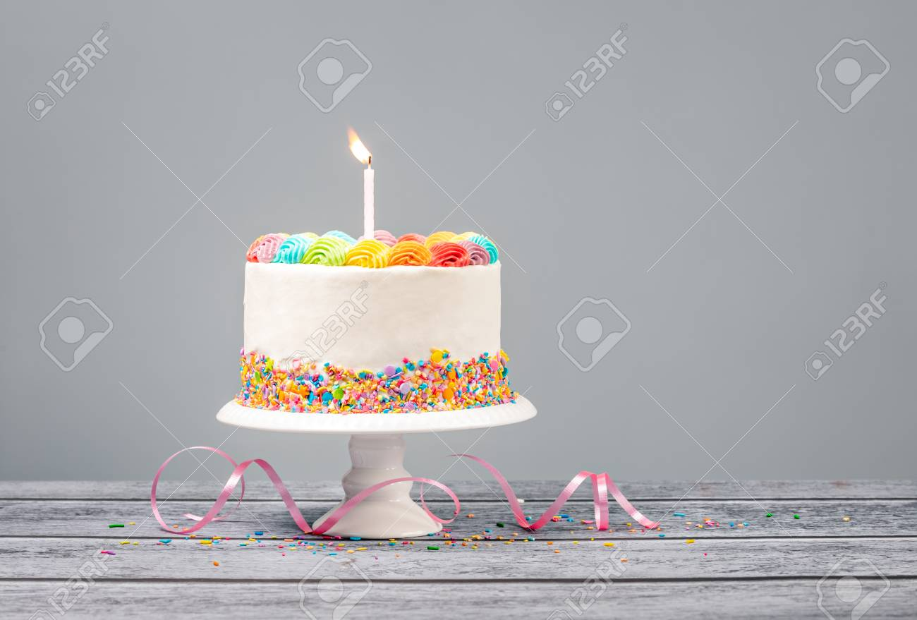 White Birthday cake with rainbow icing, colorful Sprinkles and one candle over a gray - 121745943