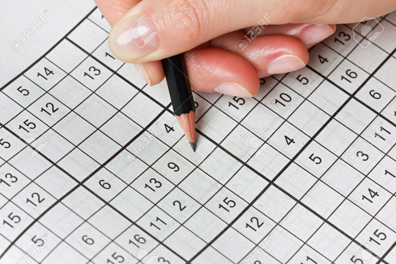 Crossword images stock pictures royalty free crossword photos woman hand holding a pencil and solves crossword sudoku popular puzzle game with numbers stock biocorpaavc
