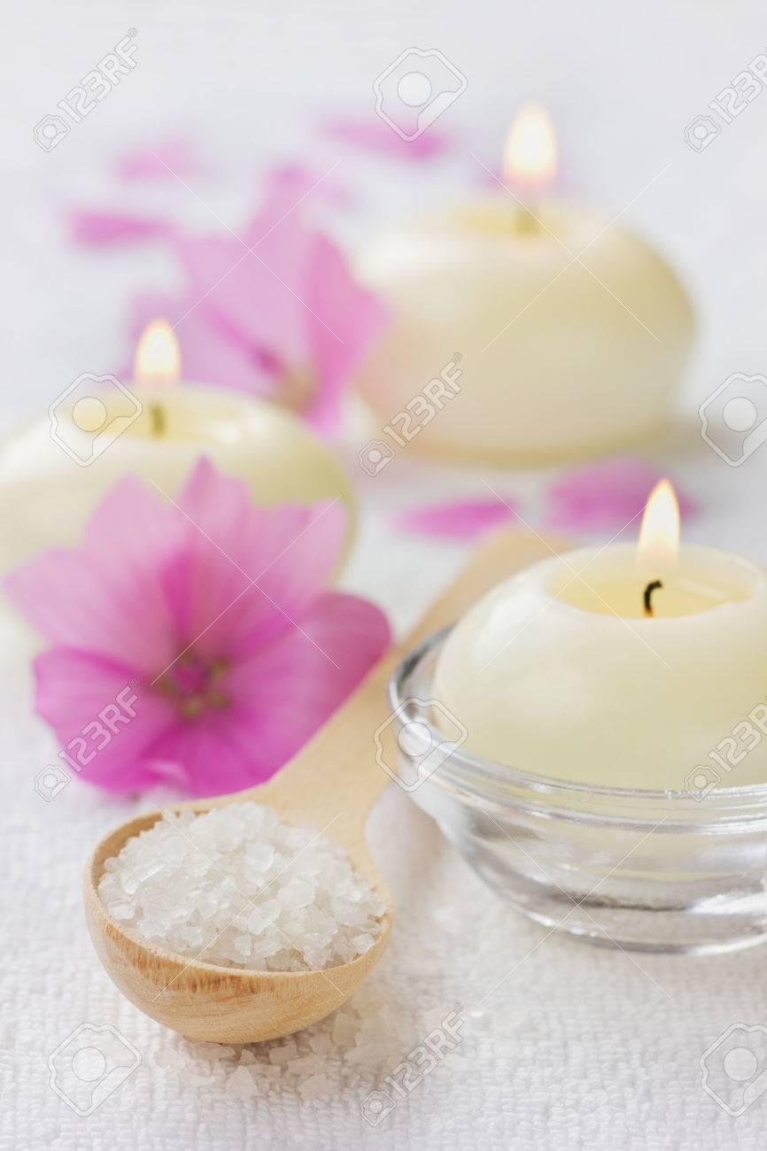archivio fotografico composizione spa con bagno di sale marino del cucchiaio di legno fiori rosa e candele accese su una superficie bianca