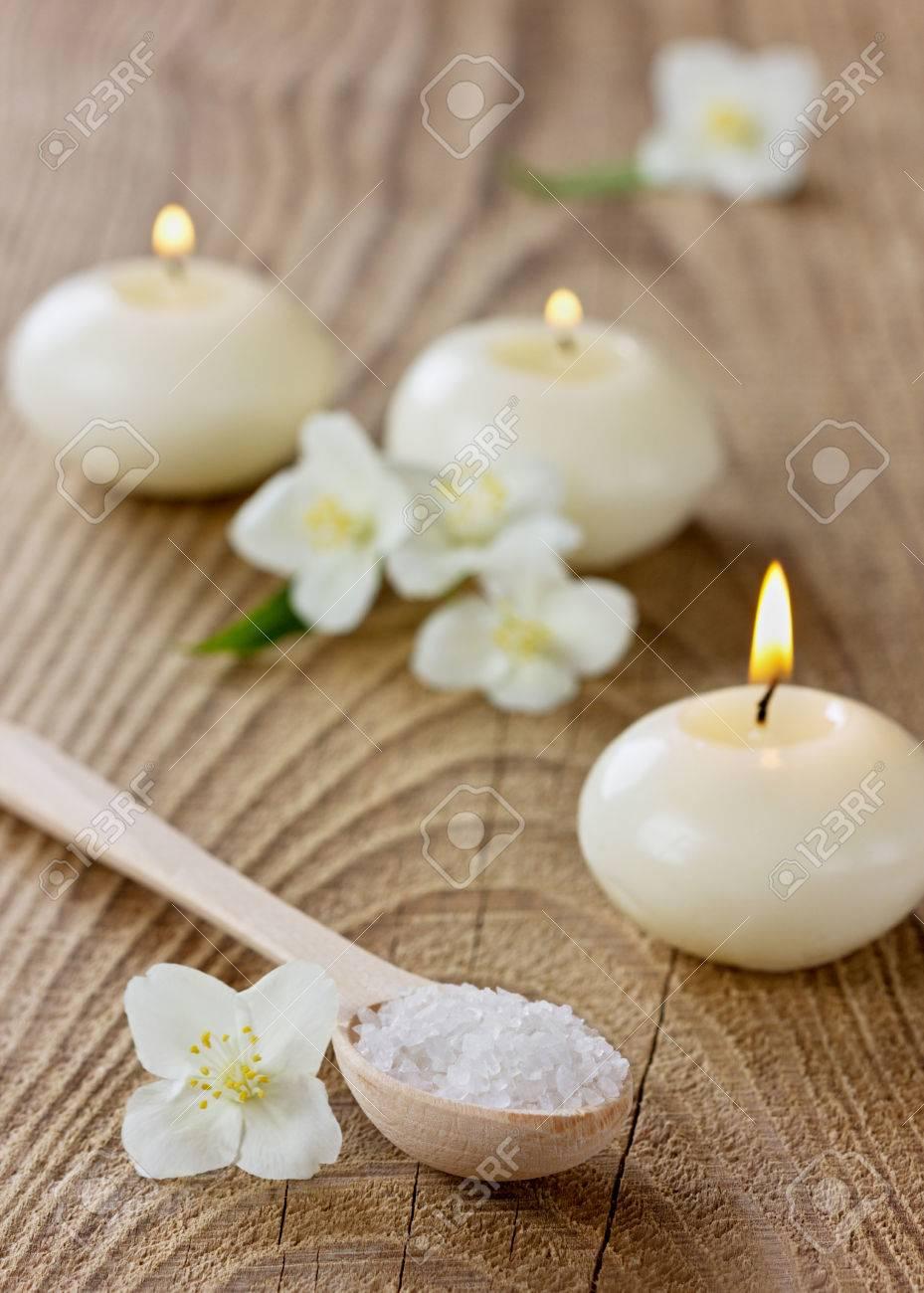 archivio fotografico composizione spa con bagno di sale marino del cucchiaio di legno fiori di gelsomino e candele accese su una superficie rustica