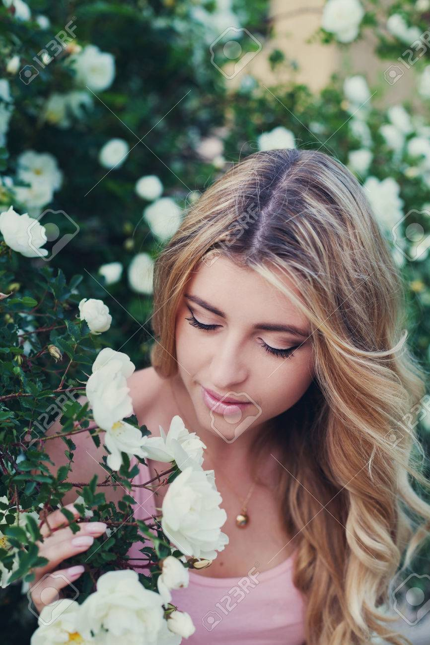 Beautiful woman with long curly hair smells white roses outdoors beautiful woman with long curly hair smells white roses outdoors closeup portrait of sensual girl izmirmasajfo Image collections