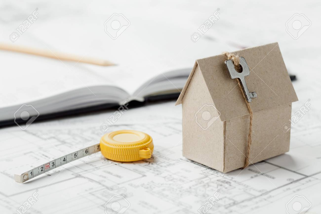 Model of cardboard house with key and tape measure on blueprint model of cardboard house with key and tape measure on blueprint home building architectural malvernweather Images