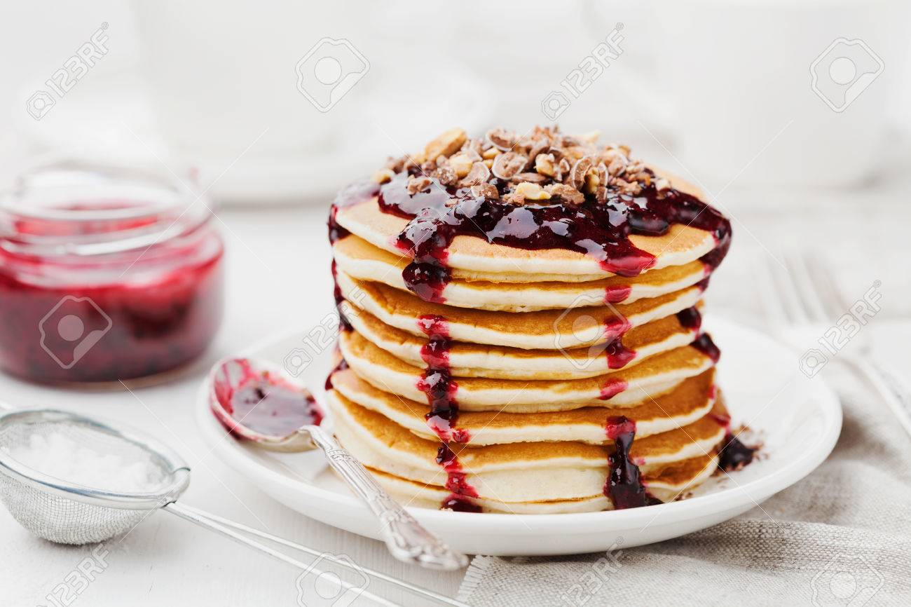 Stack of american pancakes or fritters with blackcurrant jam in plate on white table, delicious dessert for breakfast - 51357064