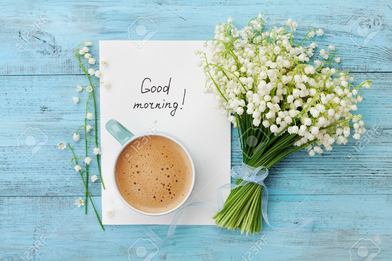 Coffee mug with bouquet of flowers lily of the valley and notes good morning on turquoise rustic table from above, beautiful breakfast, vintage card, top view, flat lay - 58821365