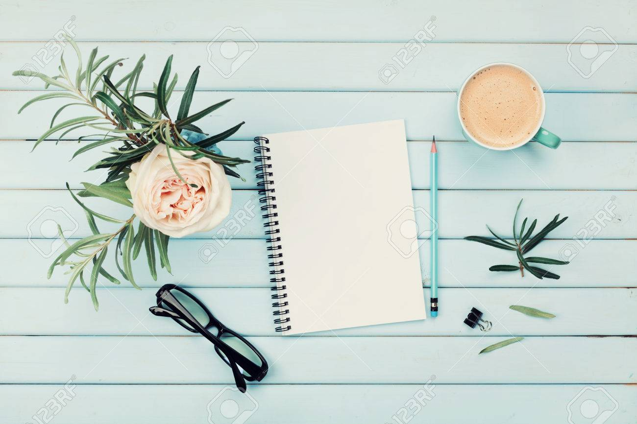 Morning coffee cup, clean notebook, pencil, eyeglasses and vintage rose flower in vase on blue rustic table top view. Planning and design concept. Cozy breakfast. Flat lay styling. - 63440135