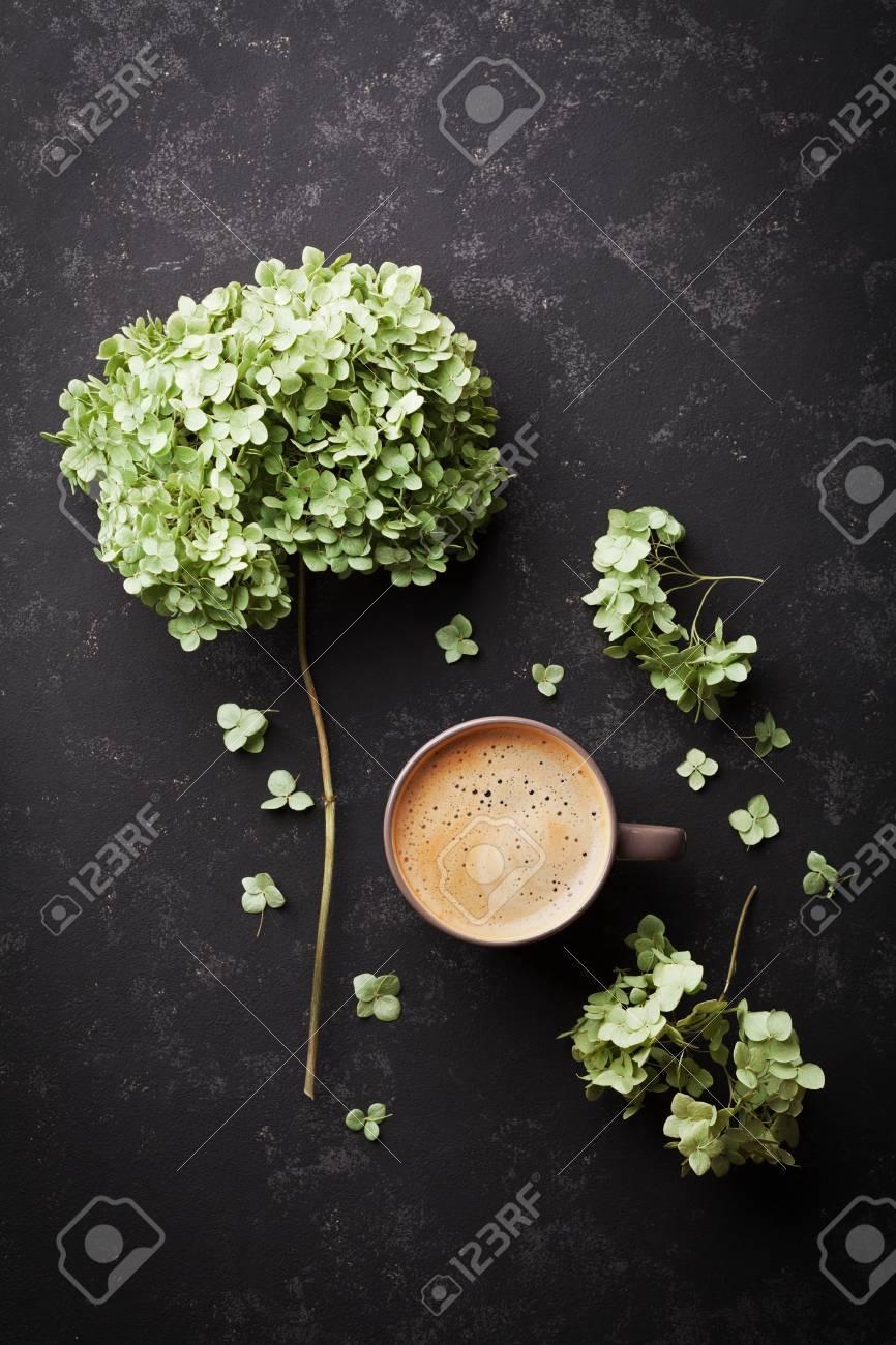Fiori Di Ortensia Secchi composizione con tazza di caffè e fiori secchi ortensia sul tavolo nero  d'epoca dall'alto, distesi