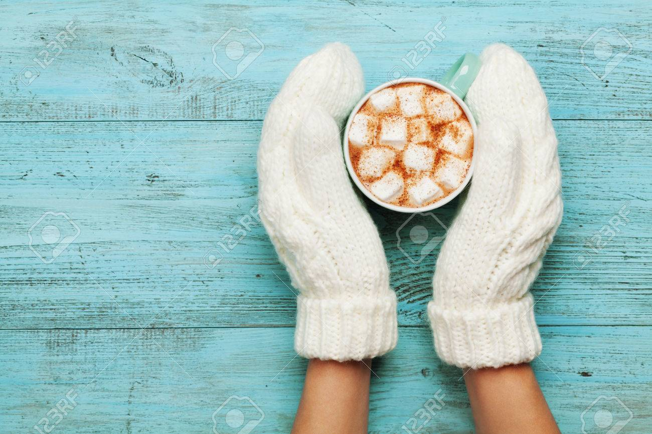 Woman hands in mittens hold cup of hot cocoa or chocolate with marshmallow on turquoise vintage table from above. Flat lay style. - 63908002