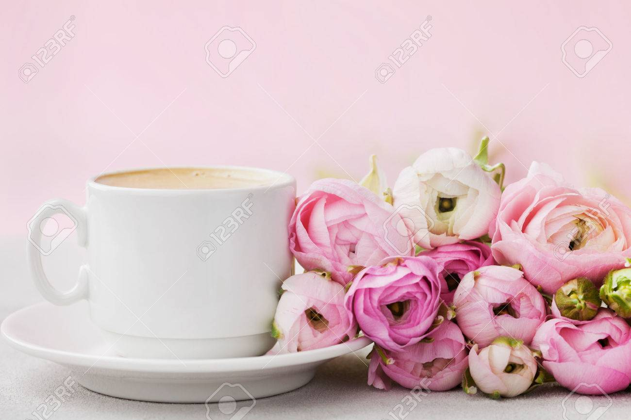 Beautiful spring Ranunculus flowers and cup of coffee on gray stone table. Pastel color. Greeting card for Valentines or Womans Day. Breakfast. Empty space for text. - 69005246