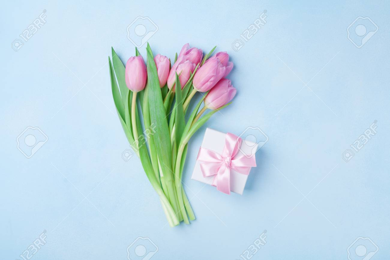 Spring tulip flowers and gift box on blue pastel table top view. Greeting card for Birthday, Womans or Mothers Day. Flat lay. - 95246028