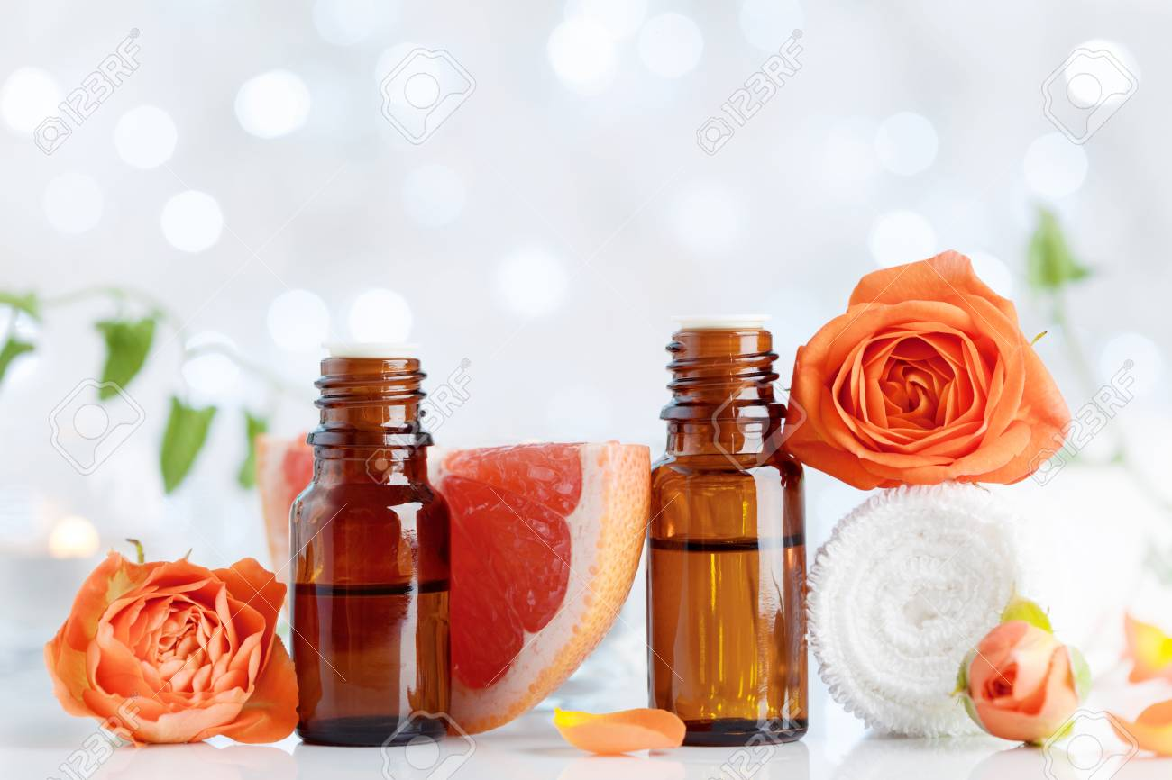 Essential oil bottles with towel, grapefruit and rose flowers on white table. Spa, aromatherapy, wellness, beauty background. Bokeh effect. - 106738405