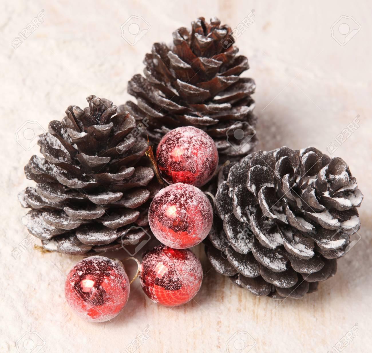 Drie Besneeuwde Dennenappels En Rode Kerstballen Royalty Vrije Foto