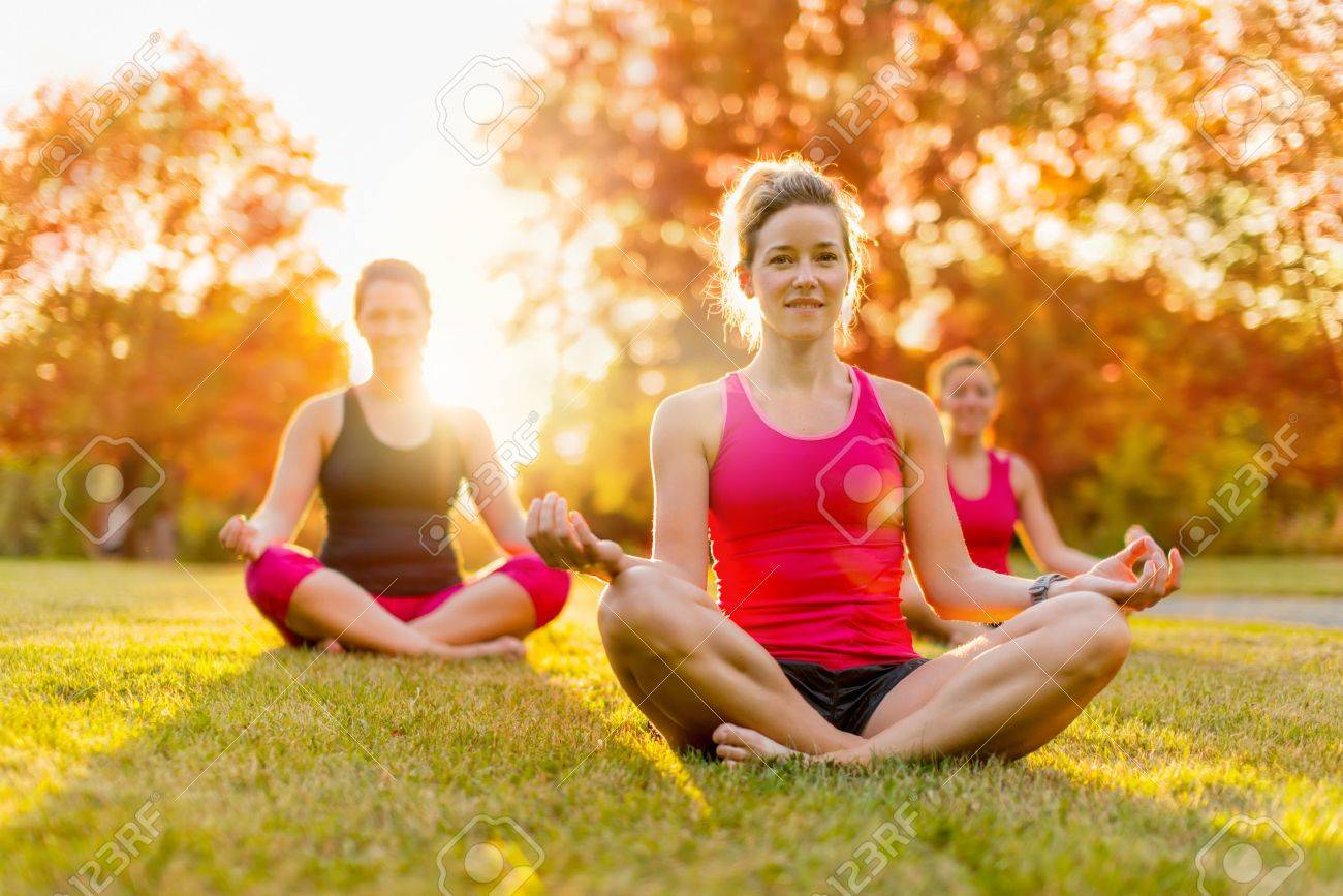horizontal detail of a group of women doing yoga outdoors at sunset with lens flare. Shallow depth of field - 31668218