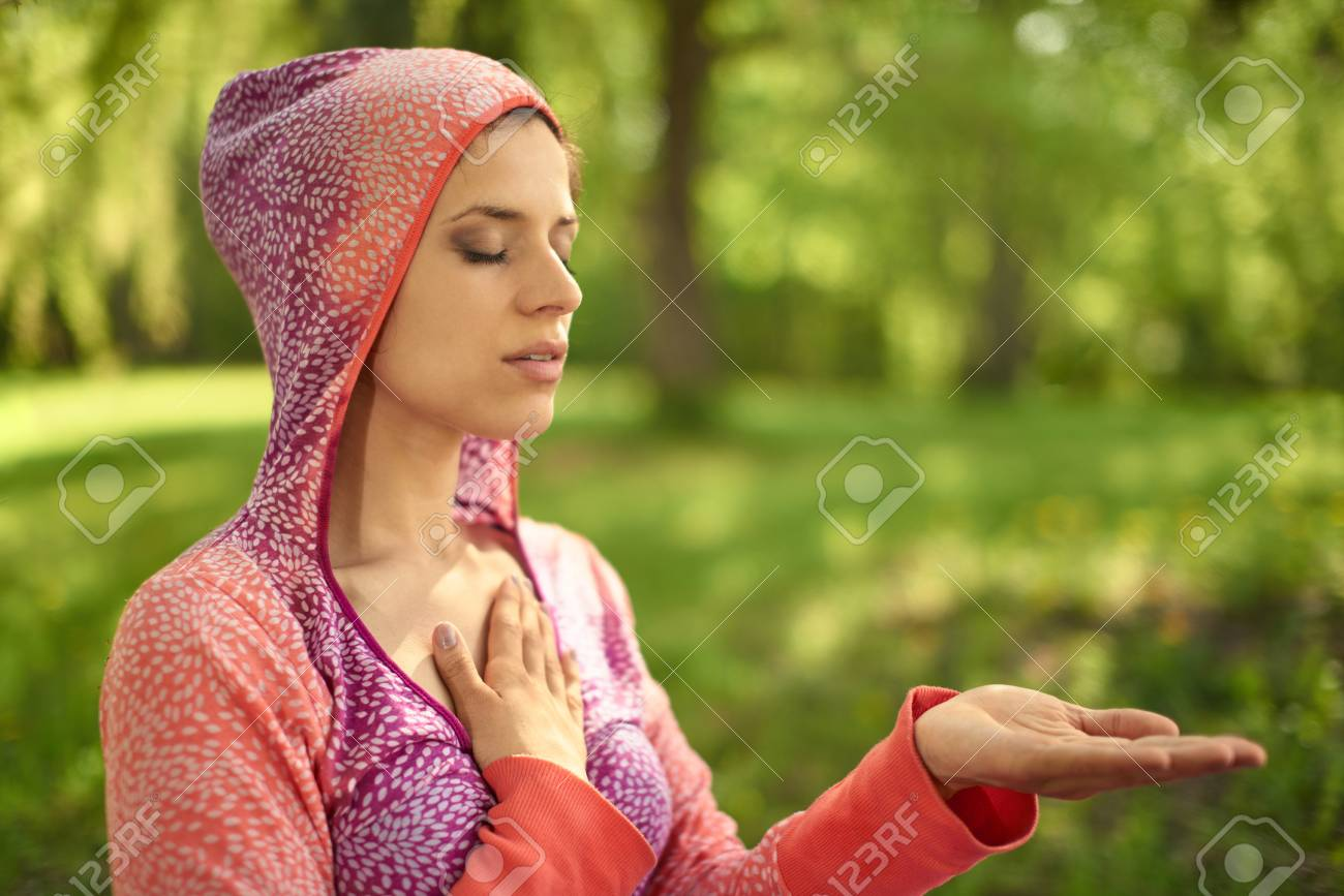 Portrait of beautiful mixed race caucasian, african, middle eastern girl meditating and doing yoga at sunset on the grass in a park or forrest - 52846947