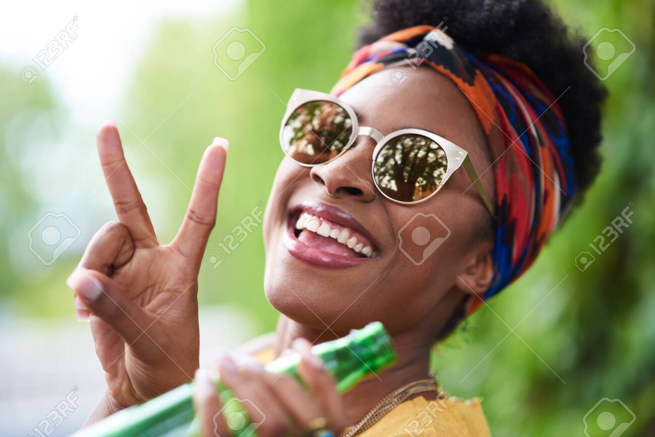 Attractive young african american woman having a drink listening - 135176799