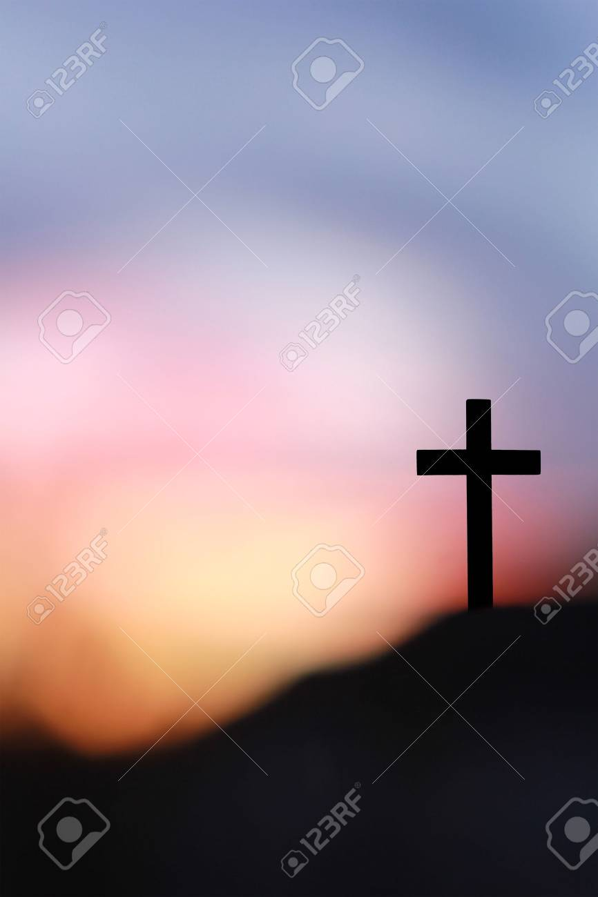 The Cross of Jesus Christ on the rock against blurry sunrise
