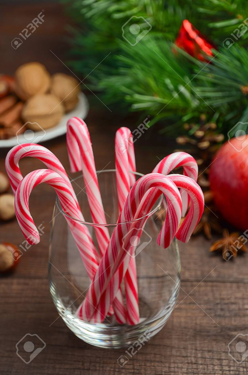 peppermint candy canes and other christmas decorations on wooden background stock photo 63034634