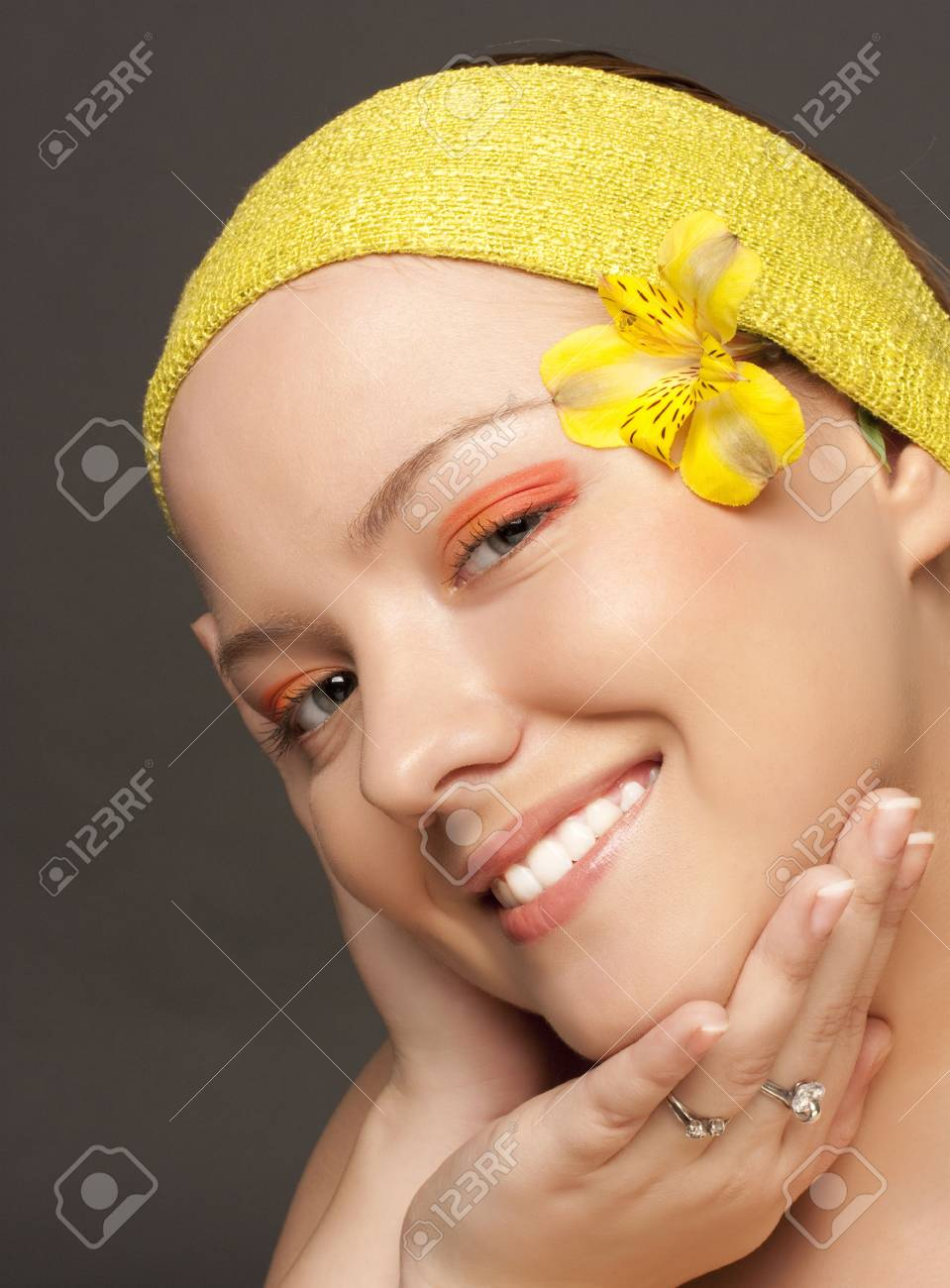 beautiful smiling girl with a yellow flower and a yellow scarf on a grey background Stock Photo - 6147113
