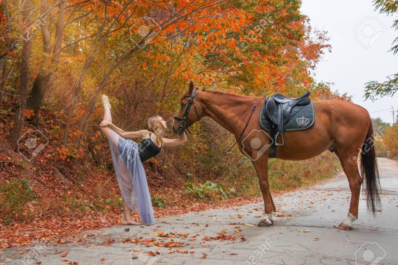 junger schöner tänzer, werfend mit einem pferd im holz, flexibler