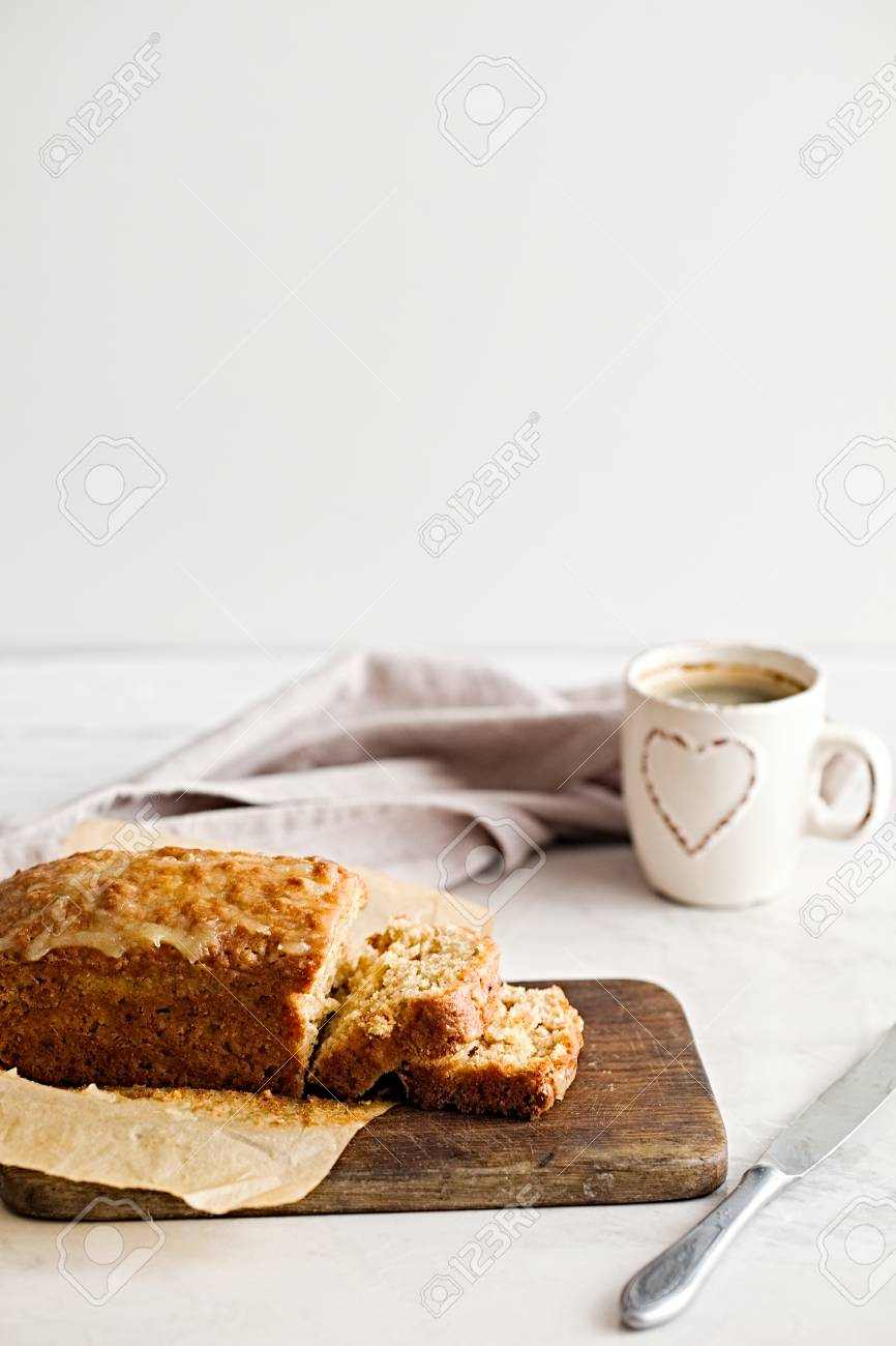 Cut of glazed applesauce oatmeal bread on a white marble table