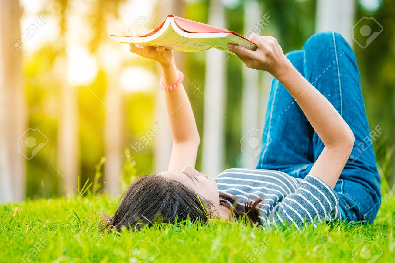 Asian teenage girl reading a book in the park on Sunday morning, a brilliant weekend. The women students are reading books, intended to prepare for university entrance exams. - 85118614