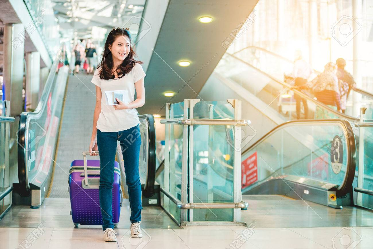 Asian women were carrying luggage around the international airport. She was traveling abroad to travel on weekends. - 85366200