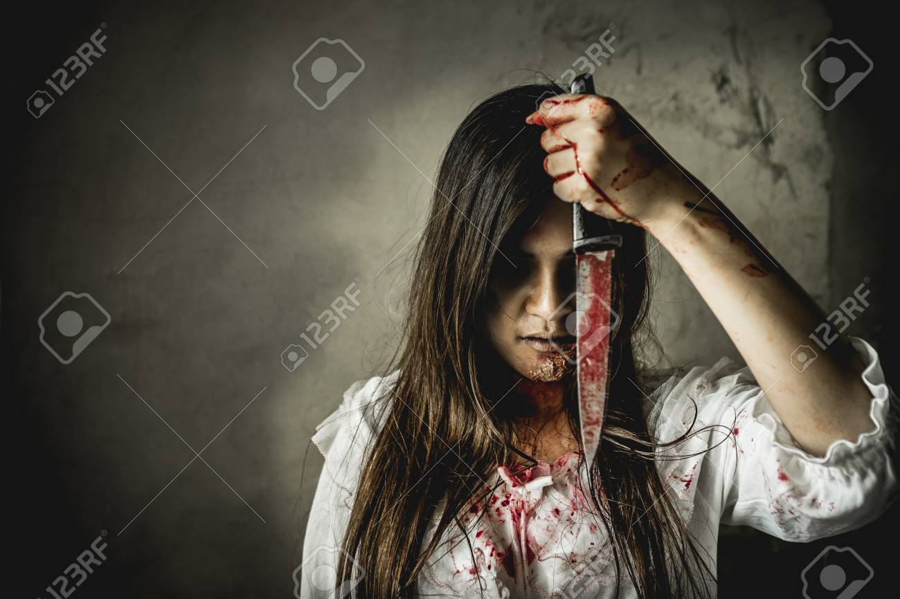 Asian girl dress killer to Halloween festival She's holding a kitchen knife and a big soaked with blood with terrible eyes ready to kill people. - 88039284