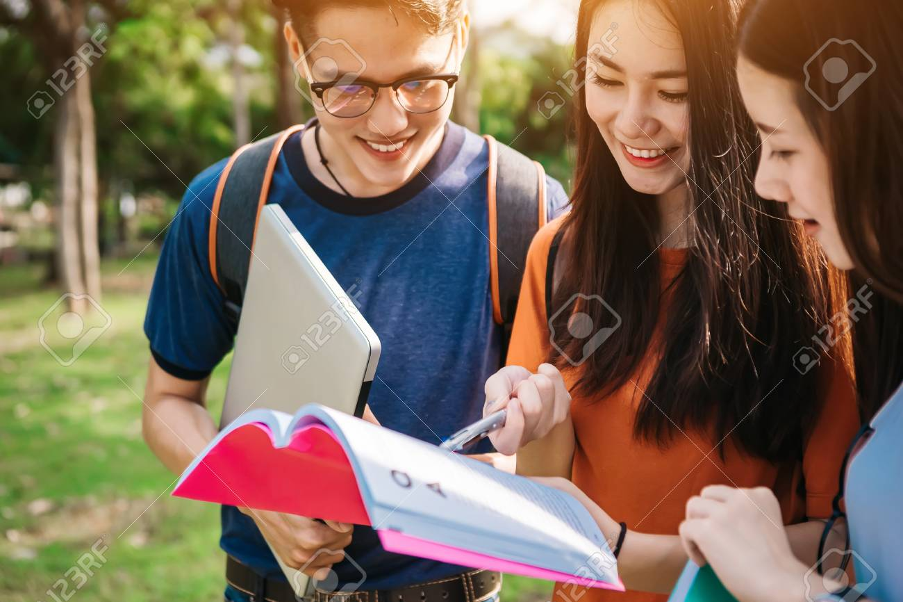 A group of young or teen Asian student in university smiling and reading the book and look at the tablet or laptop computer in summer holiday. - 91747915