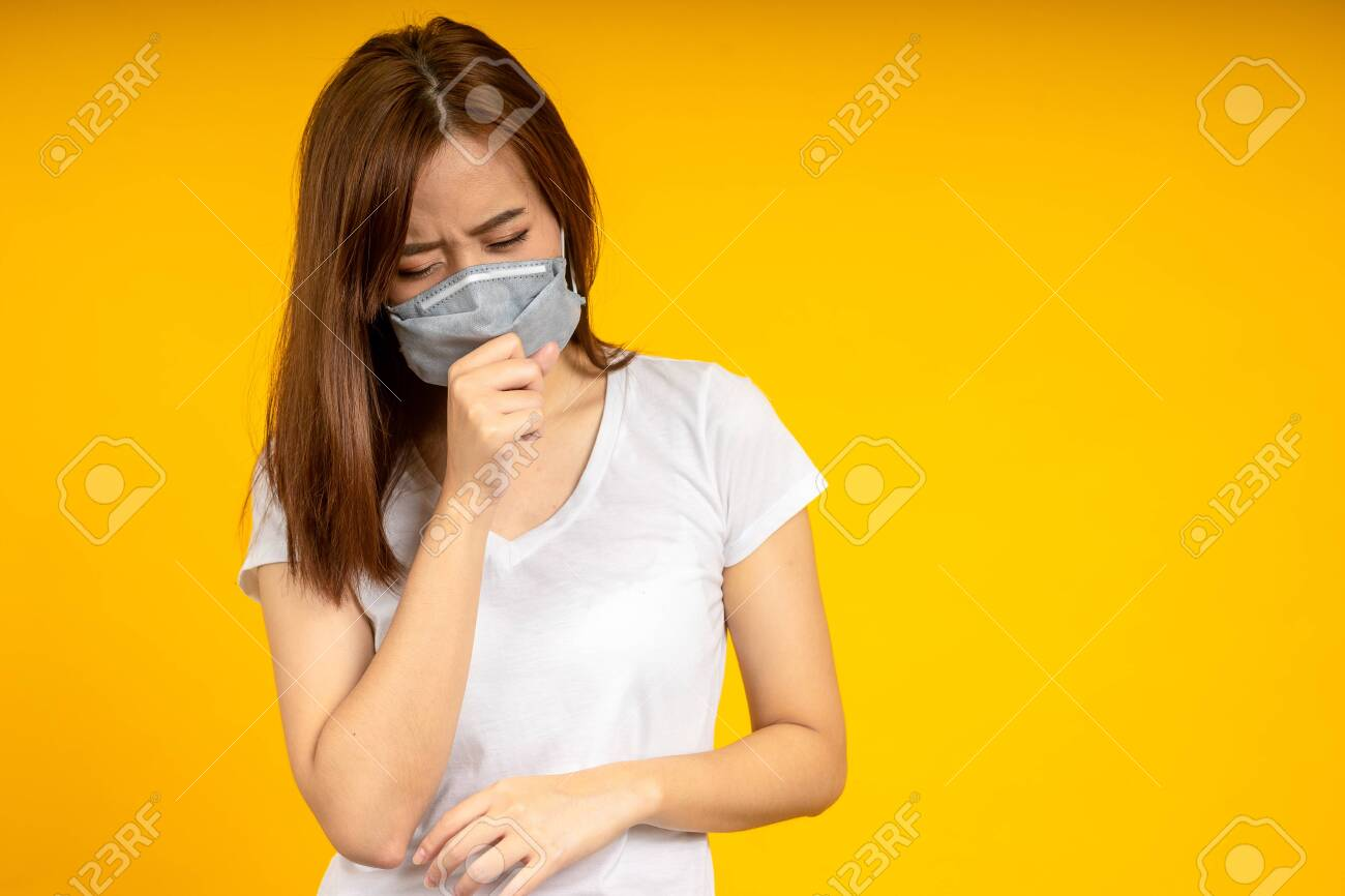 Asian woman is coughing or sneezing wearing hygienic mask to protect virus, COVID 19 or Colona Virus infection and dust PM 2.5 pollution isolate on yellow background - 144033984