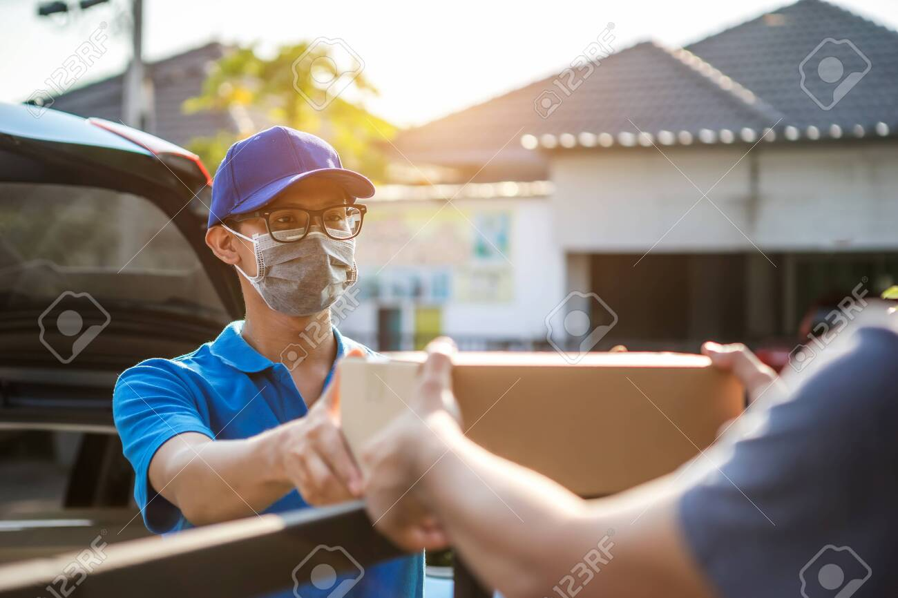 Asian delivery man wearing mask delivers parcel, customer in medical gloves signs on tablet. Delivery service under quarantine, disease outbreak, coronavirus covid-19 pandemic conditions. - 144881189
