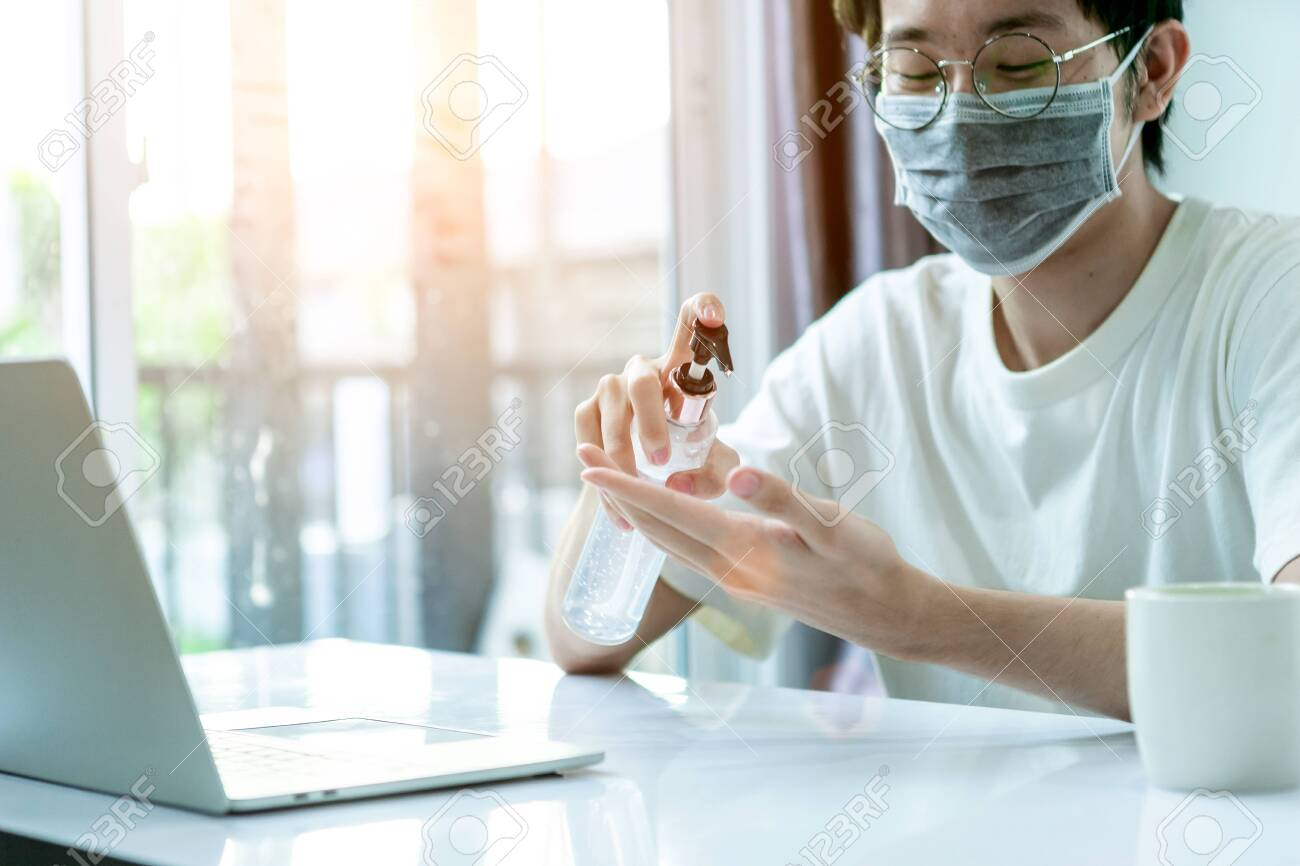 Asian man working from home, he use laptop and tablet and drinking coffee in covid-19 virus situation. Her working in quarantine for coronavirus. Work from home concept. - 147906476