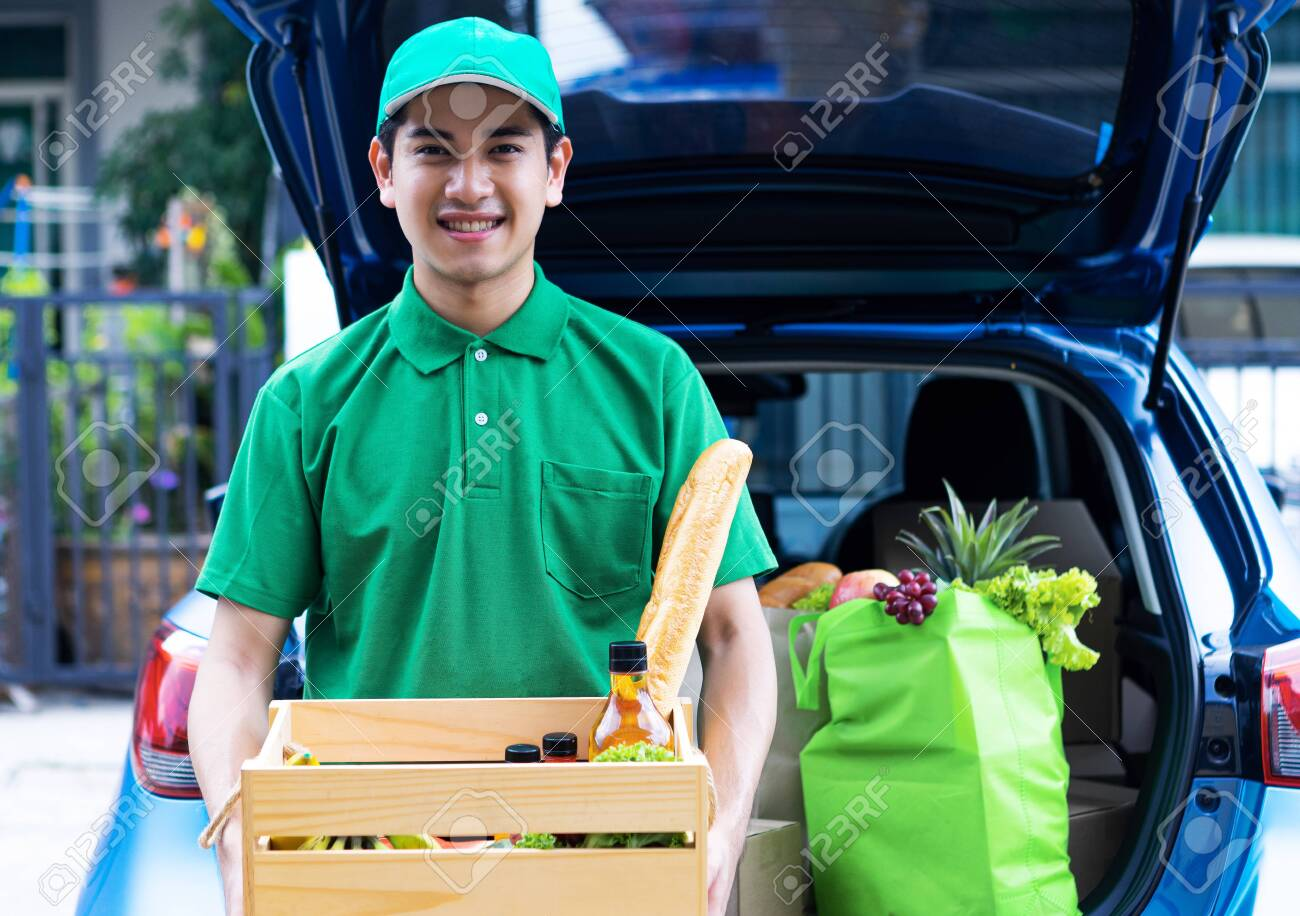 Asian delivery man in green t-shirt delivering food, fruit, joice and vegetable to home - online grocery shopping service concept - 148856528