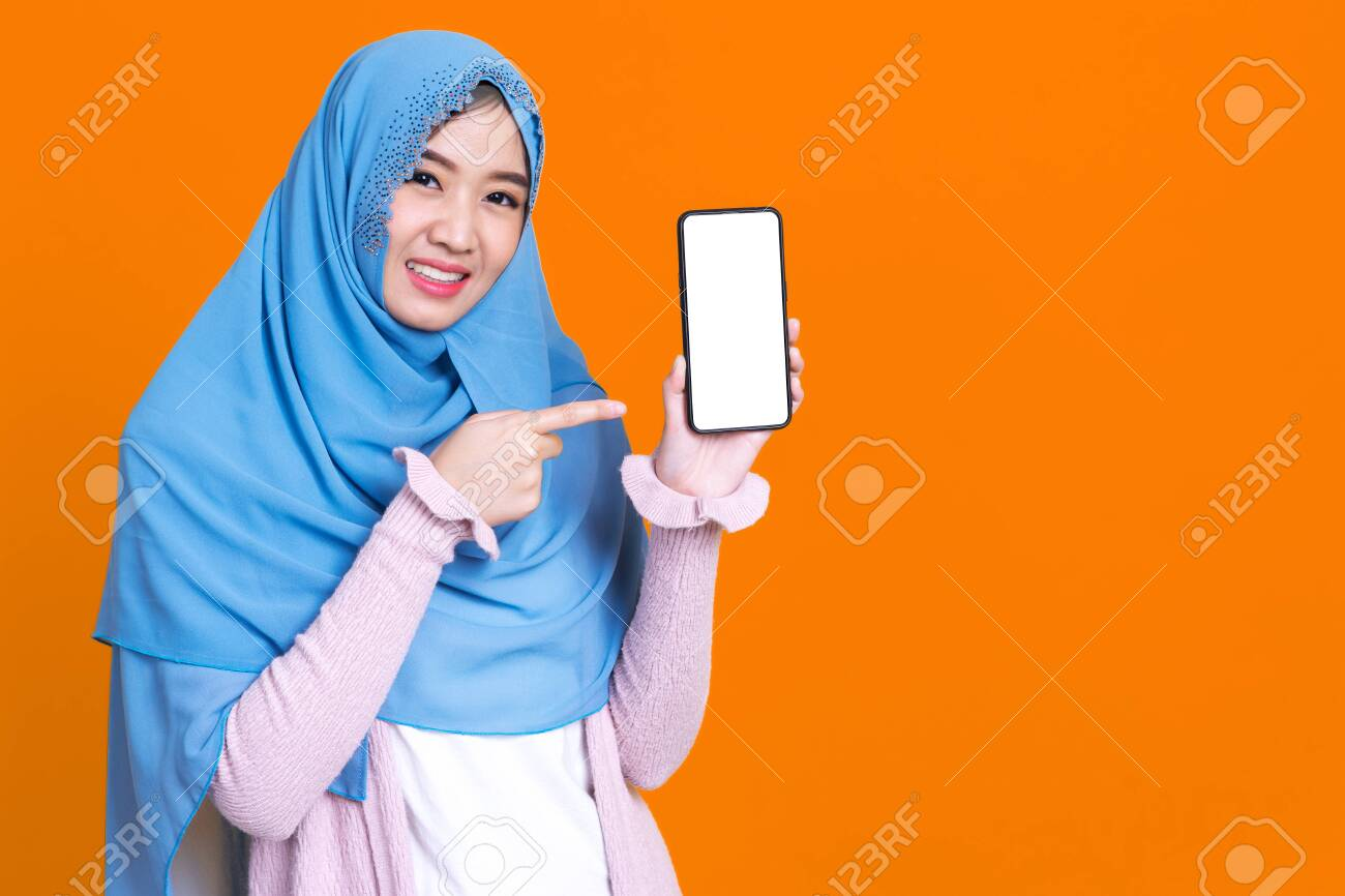 Photo of islamic woman in hijab headscarf wearing mask with oriental makeup use smartphone and credit card over orrange isolate background - 148856616